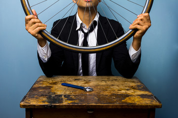 Man in suit trying to fix a bicycle tyre