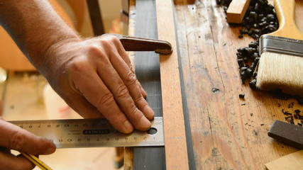 Luthier pointing the frets of a guitar