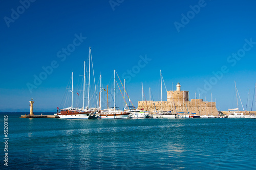 Yachts and old lighthouse in the harbor of Rhodes,Greece.