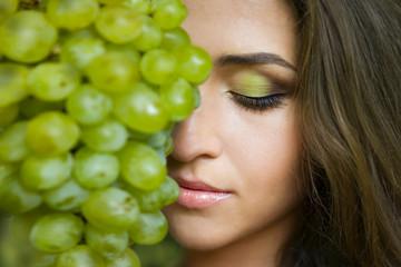 Девушка с красивым макияже и виноградом