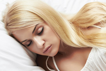 sleeping beautiful blond girl. beauty woman. white bed