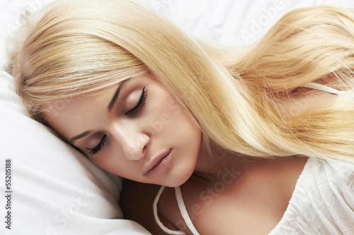 sleeping beautiful blond girl. beauty woman. white bed