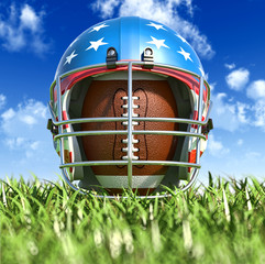 American football helmet over the oval ball, on the grass. Front