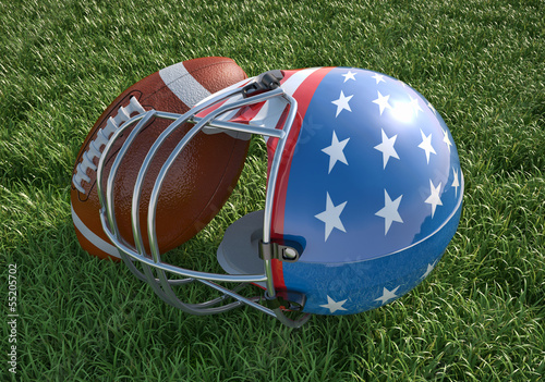 American football helmet and ball, on the grass. Close up.