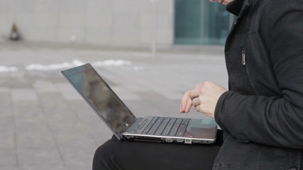 Closeup young man with laptop outdoors