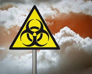 Yellow biohazard warning sign on against dark cloudy sky.