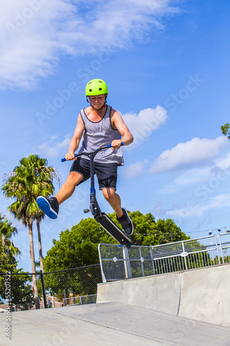boy has fun riding his push scooter at the skate park