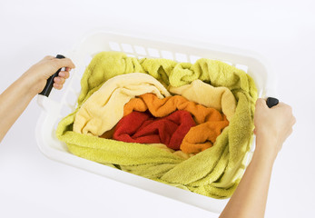 woman holding a basket with color laundry to wash