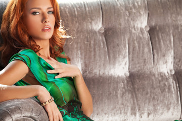 Red hair beauty. Beautiful young red hair woman sitting on the c