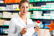 Female pharmacist in pharmacy with medicament