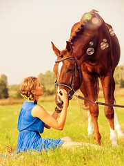 young nice  girl  with  horse in the meadow