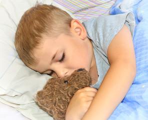 Little boy sleeping with his teddy bear