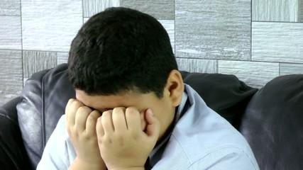Allergic boy scratching his eyes