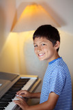 Young boy plays a piano