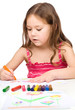 Little girl is drawing using a crayon