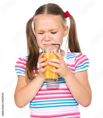 Little girl unwillingly drinking orange juice