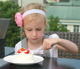 Cute little girl eating cake in outdoor cafe
