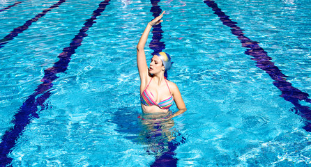 Synchronized swimmer in pool exercizing