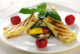 Grilled Halloumi cheese on grilled vegetables with basil