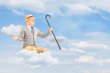 Senior man floating on a cloud and spreading arms against cloudy