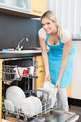 Woman Putting Dishes In The Dishwasher