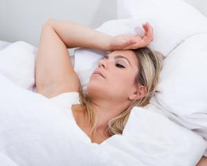 Upset woman lying on bed
