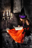 Little girl witch with a book in her hands and candles on hallow