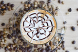 top of view of a cup of latte art with coffee beans on table