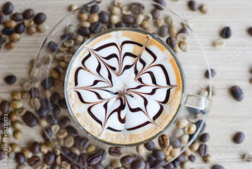 Fototapeta top of view of a cup of latte art with coffee beans on table