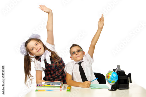 a boy and a girl at the desk raised their hands