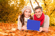 autumn couple with tablet online