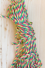 Bundles of colorful rope on wood background