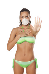 girl with a breathing mask in a bikini showing stop sign