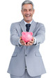 Wide smiling businessman holding piggy bank