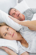 Tired wife blocking her ears from noise of husband snoring looki
