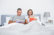 Happy couple sitting in bed reading books