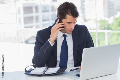 Concentrated businessman having a phone call and working on his