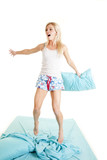 Woman jump on bed hold pillow