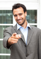 Pointing businessman in fornt of his office