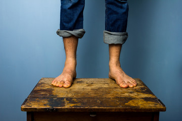 Man with bare feet standing on old wooden table