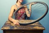 Young woman repairing bicycle wheel