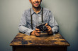 Hipster with vintage camera at old desk