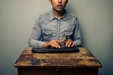 Man typing on keyboard at old desk