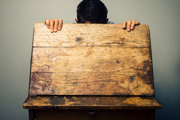 Man looking inside old school desk