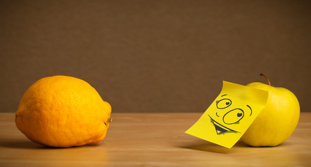 Apple with post-it note looking curiously at lemon