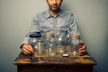 Man with empty jars at old desk