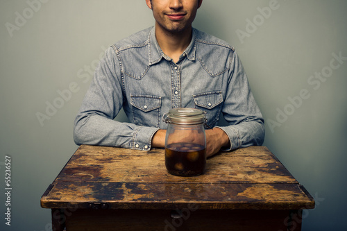 Man with jar of pickled onions at old desk