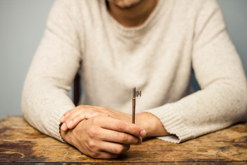 Man at table holding a key