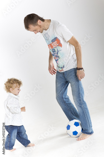 Father is teaching his toddler son to play soccer