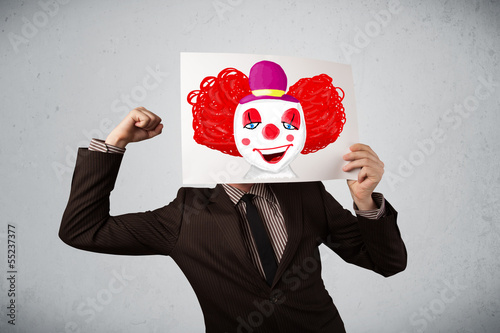 Businessman holding a cardboard with a clown on it in front of h